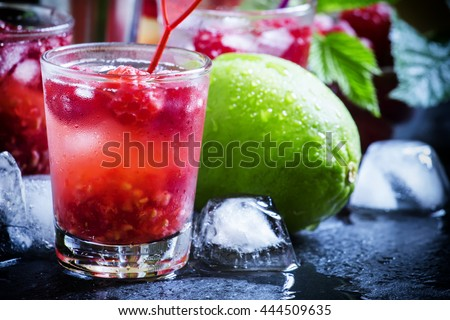 Alcoholic cocktail raspberry ambitions, with vodka, cranberry juice, soda, lime, berries and ice, bar tools, black background, selective focus - stock photo
