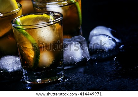 Alcoholic cocktail rum cola with ice, lime, lemon, cola and white rum, dark background, selective focus - stock photo