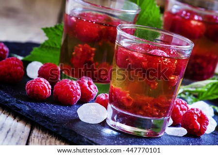 Alcoholic cocktail with whiskey, sugar and raspberries, selective focus - stock photo
