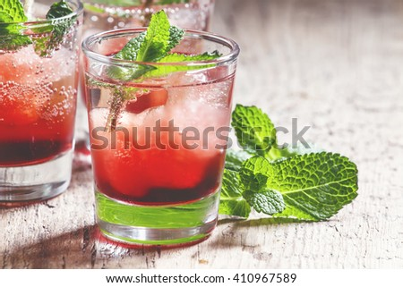 Alcoholic cocktail with white rum Bacardi, Campari, vermouth, mint and ice cubes, vintage wooden background, selective focus - stock photo