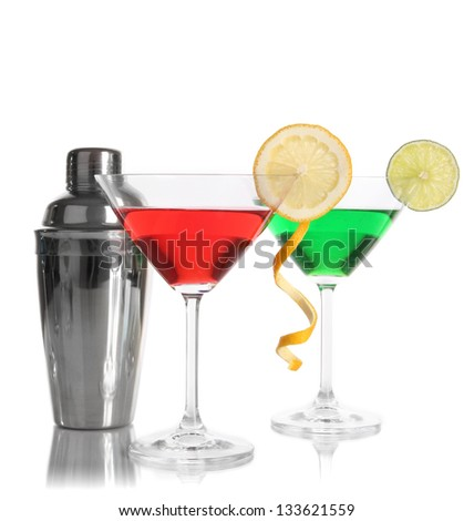 Alcoholic cocktails in martini glasses with shaker isolated on white - stock photo