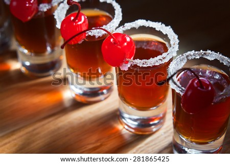 alcoholic drink with cherries on wooden table - stock photo