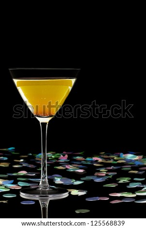 Alcoholic drink with confetti isolated over black background - stock photo
