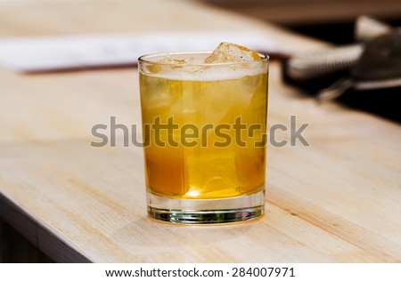 Alcoholic drink with ice in a glass on the bar - stock photo