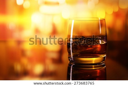 alcoholic drink with ice on a glass table in bar - stock photo