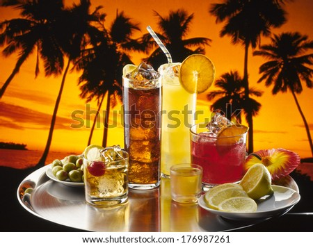 Alcoholic drinks on the beach at sunset. - stock photo