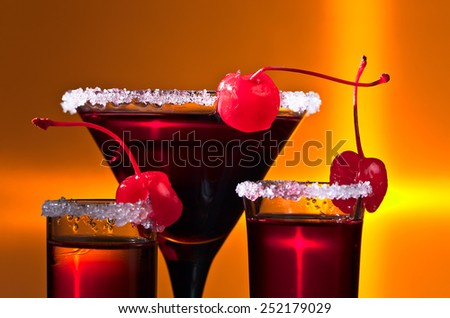 alcoholic drinks with sweet cherry on yellow background - stock photo