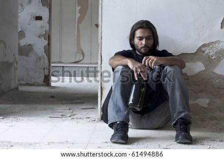 Alcoholic Sitting on the Floor - stock photo