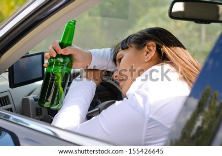 Alcoholic woman driver passed out in the car with her head resting on her arm on the steering wheel and her bottle of booze clasped in her hand - stock photo