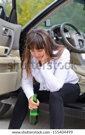 Alcoholic woman driver stopping for a drink of bear from a a bottle sitting on the sill in the open door of her car with her head resting on her hand - stock photo