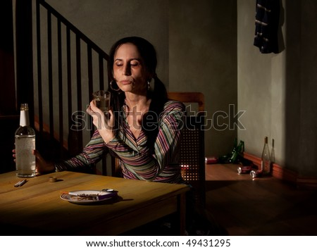 Alcoholic woman with bottle of clear liquor - stock photo