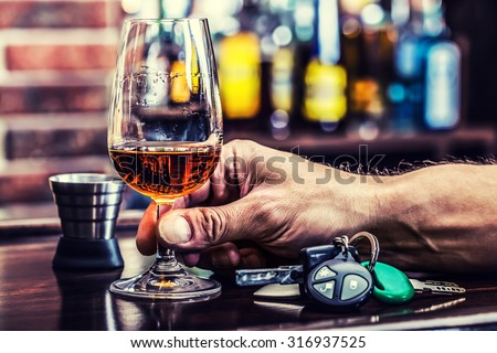 Alcoholism. Cup cognac or brandy hand man the keys to the car and irresponsible driver. - stock photo