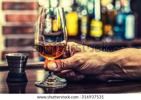 Alcoholism. Hand alcoholic and drink the distillate brandy or cognac. - stock photo