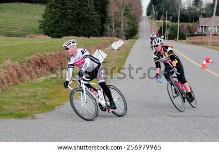 ALDERGROVE, BC/CANADA - MARCH 1, 2015: A male and female cyclist compete during the Escape Velocity Spring Series cycling race near Aldergrove, British Columbia on March 1, 2015.