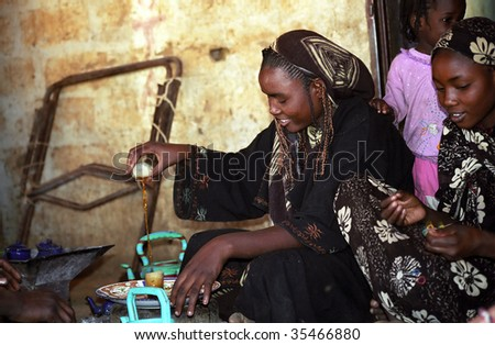 ALEG, MAURITANIA - JANUARY 6 : Two unidentified women prepare tea for the participants of Budapest-Bamako Rally January 6, 2006 in Aleg, Mauritania. - stock photo