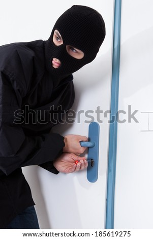 Alert thief looking away while opening door with tool during house breaking - stock photo