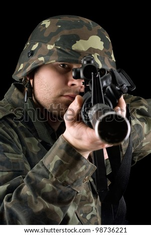 Alerted soldier pointing m16 in studio. Closeup - stock photo