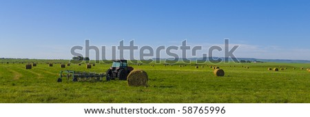 Alfalfa hay bales in a field with tractor in the Canadian prairie's, Alberta, Canada - stock photo
