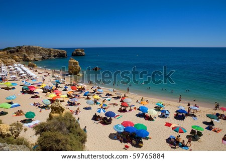 ALGARVE, PORTUGAL - AUGUST 23: Crowded beautiful beach at Sao Rafael, on August 23, 2010 in ALGARVE, PORTUGAL - stock photo