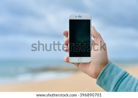 Algarve, Portugal - March 7, 2016: Closeup on hand using smart phone iPhone 6 for photo and video on ocean beach outdoors background - stock photo