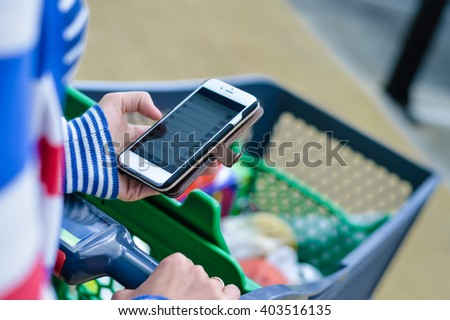 Algarve, Portugal - March 07, 2016: Female holding iPhone 6 mobile smart phone in hand during shopping. Cart on store background shopping car park.  illustrative editorial - stock photo
