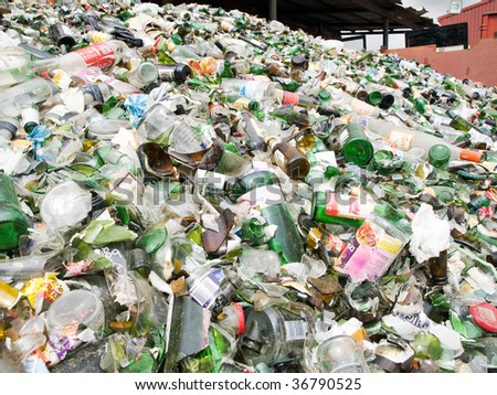 ALGECIRAS, SPAIN - AUGUST 30: Mountain of used glass bottles in a recycling plant August 30, 2009 in Algeciras. The used glass was collected in containers and will be crashed for recycling. - stock photo