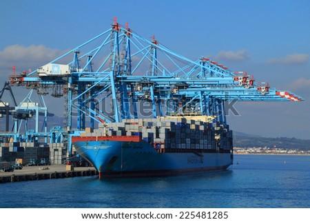 ALGECIRAS, SPAIN - DECEMBER 24: Container ship being loaded in the Mediterranean port of Algerciras, the 6th busiest container port in Europe. On December 24, 2013 in Algeciras, Spain. - stock photo