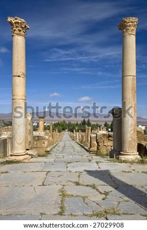 Algeria. Timgad (ancient Thamugadi or Thamugas). Cardo street and surrounding colonnade - view from forum, where Cardo crossing with Decumanus Maximus - stock photo