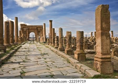 Algeria. Timgad (ancient Thamugadi or Thamugas). Decumanus Maximus street and surrounding colonnade terminated Trajan's Arch - stock photo