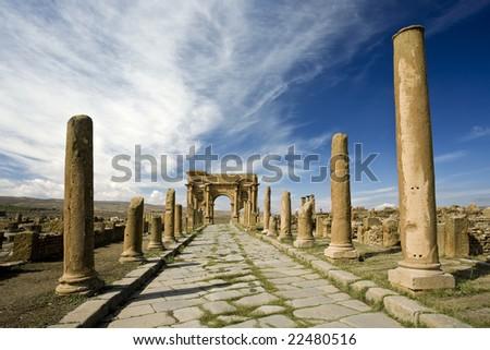 Algeria. Timgad (ancient Thamugadi or Thamugas). Decumanus street and surrounding colonnade terminated Trajan's Arch. - stock photo