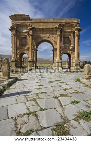 Algeria. Timgad (ancient Thamugadi or Thamugas). Paving stones of Decumanus Maximus street and 12 m high Trajan's Arch. Please see my other images of Roman places in Algeria, Tunisia and Libya - stock photo