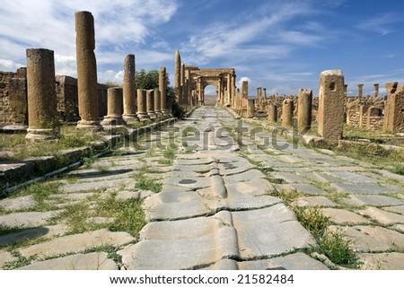 Algeria. Timgad (ancient Thamugadi or Thamugas). Paving stones of Decumanus street and Corinthian colonnade terminated Trajan's Arch. - stock photo