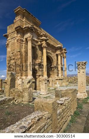 Algeria. Timgad (ancient Thamugadi or Thamugas). Triumphal arch, called Trajan's Arch (Corinthian order with three arches) - stock photo