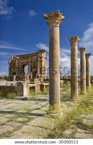 Algeria. Timgad (ancient Thamugadi or Thamugas). View on Trajan's Arch via the Sertius market with stone stalls surrounded by Corinthian columns - stock photo