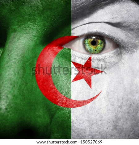 Algerian flag painted on a man's face to support his country Algeria - stock photo