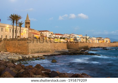 Alghero, Sardinia Island, Italy in the sunset. Defensive city wall. Mediterranean sea in the foreground. - stock photo