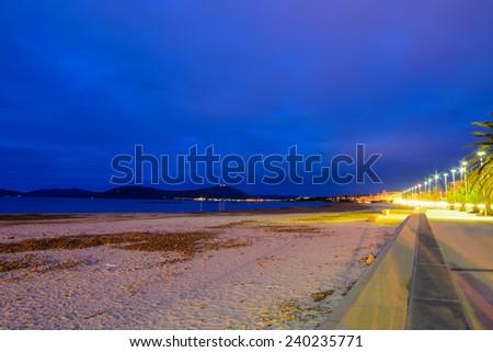Alghero shore under a blue sky at night - stock photo