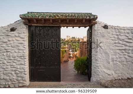 Alhambra seen through doors in the old town of Granada