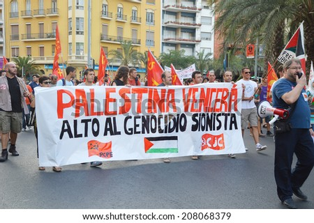 "ALICANTE, SPAIN - JUL 24: Protesters holding banner ""Palestine will overcome the genocide"" marched past Plaza del Luceros protesting against Israel killing Patestianans. Alicante Jul 24, 2014  - stock photo"