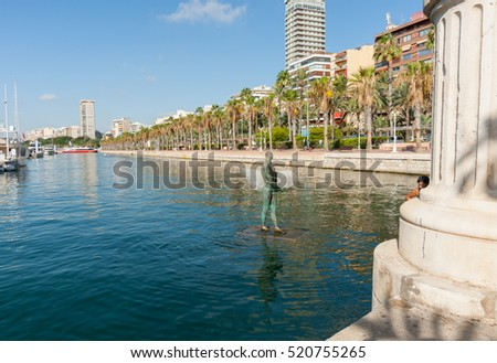 ALICANTE, SPAIN - SEPTEMBER 9; Icarus with broad shoulders with little head carrying a surf board in marina harbor with city skyline backdrop, September 9, 2016, Alicante, Spain