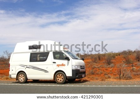 ALICE SPRINGS, NORTHERN TERRITORY, AUSTRALIA - December 2. Recreation Vehicle drives on the Stuart Highway between red sand dunes in the desert on December 2, 2015 in Alice Springs.  - stock photo
