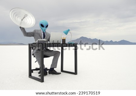 Alien businessman sitting at his office desk trying to communicate holding up a satellite dish - stock photo
