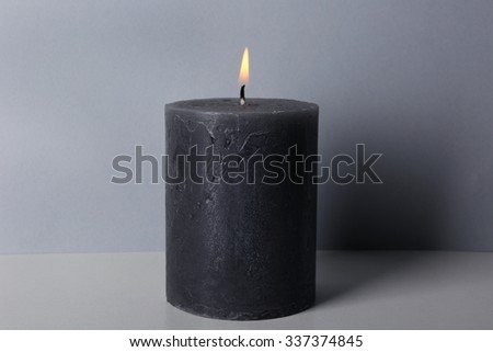 Alight wax grey candle on light background - stock photo