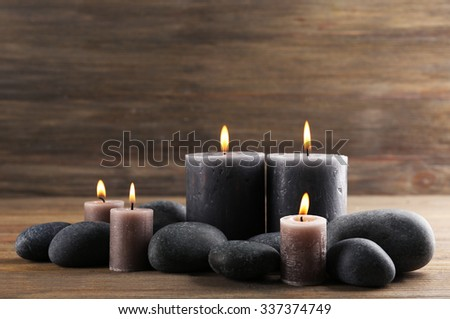 Alight wax grey candle with pebbles around on wooden background - stock photo