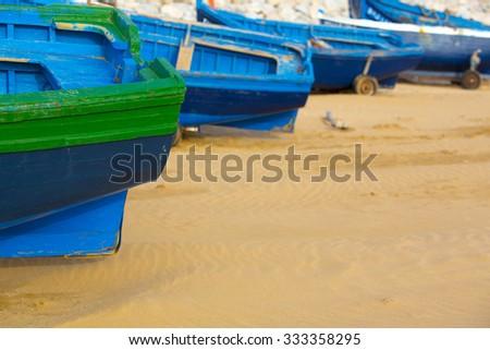 Aligned blue fishing boats standing on the beach of Sidi Kaouki near Essaouira in Morocco. - stock photo
