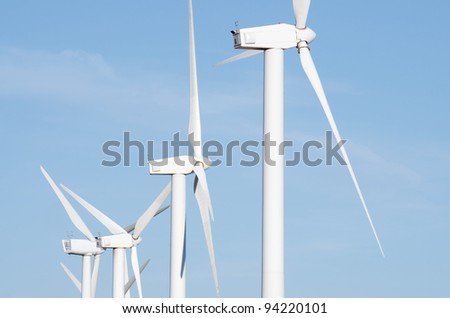aligned group of windmills for electric power production - stock photo