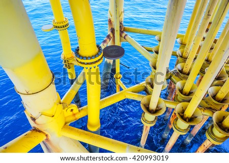 Aligned Oil and Gas Pipeline and Production slots on the sea background in Offshore wellhead remote platform, Energy and petroleum industry. - stock photo
