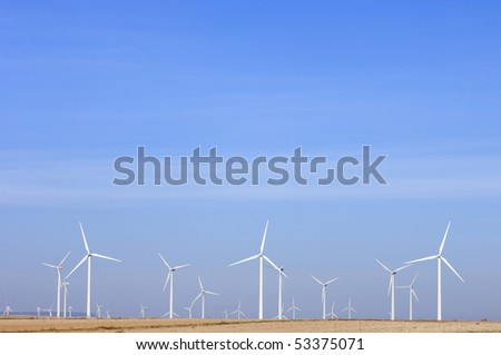 aligned windmills and blue sky in spain