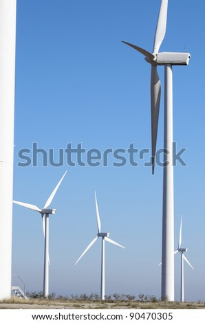 aligned windmills for renewable electric production with clear sky - stock photo