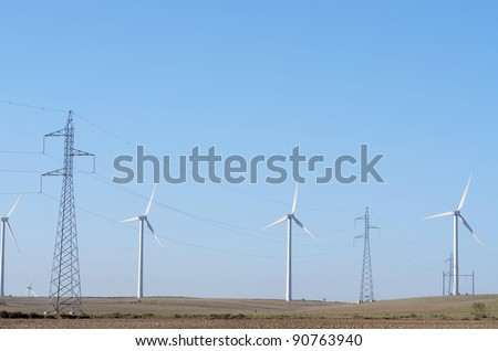 aligned windmills for renowable electric production and power line - stock photo